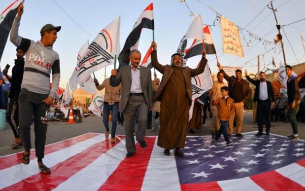 Iraqi protesters in Najaf denounce the US air strikes on several bases near the border with Syria