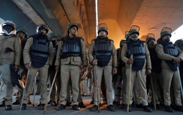 Police in riot gear keep watch during a protest against a new citizenship law in New Delhi's Seelampur area
